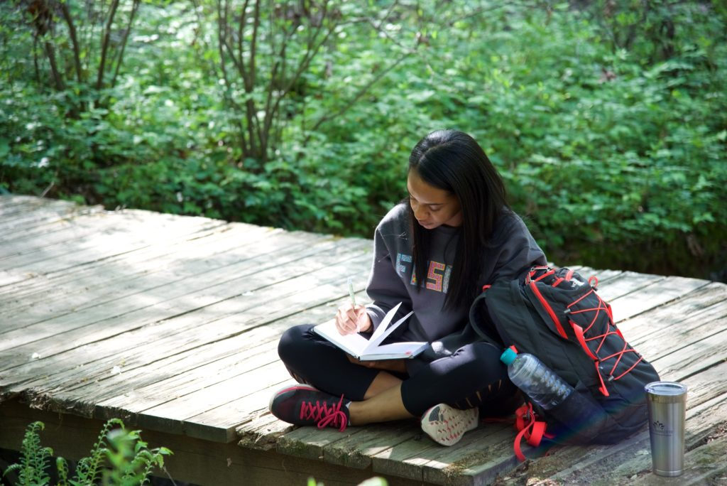 student writing in journal in Botanical Gardens