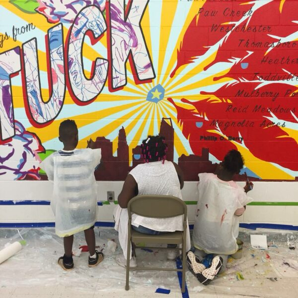 people painting mural that says Tuck