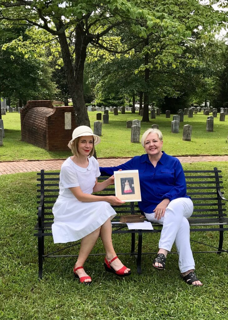 Karen Cox and Lucy Worsley on a bench in a cemetery.